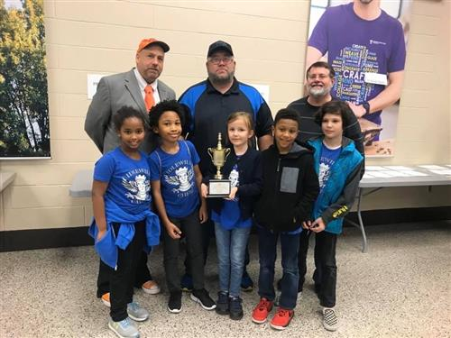 Chess team with trophe and coaches